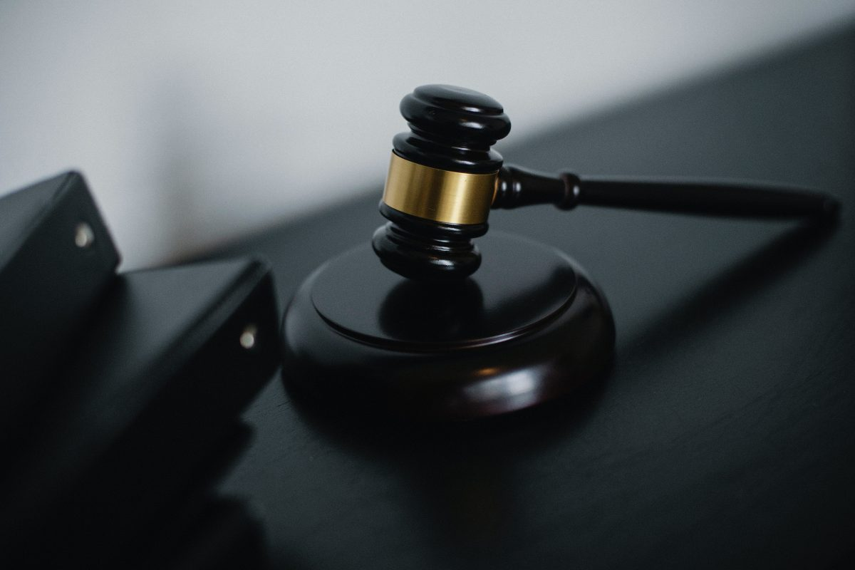 small judge gavel placed on table near folder