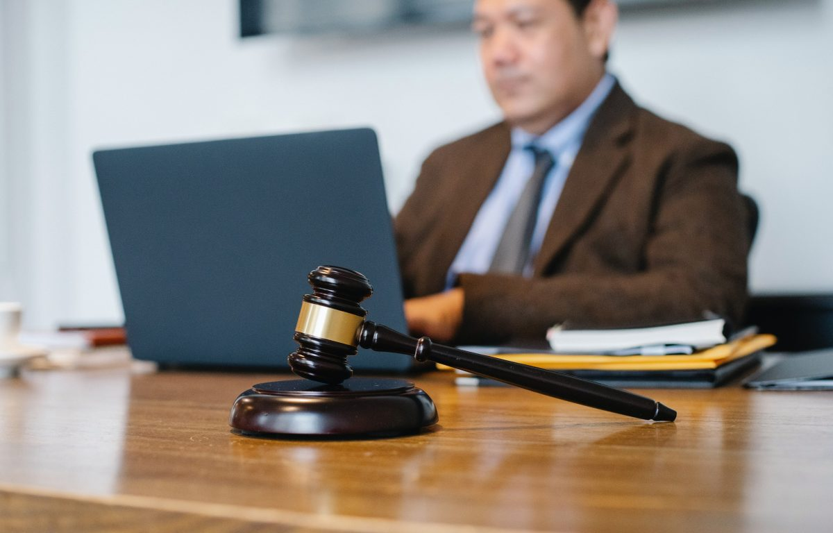 Asian judge working on laptop with gavel on table