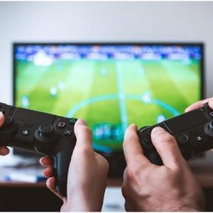 2 playstation controllers with football on tv