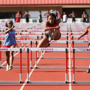 Clinton High School Track Athlete Jumps Hurdle