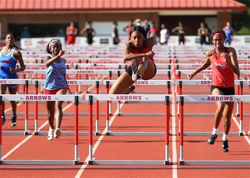 Clinton High School Track Athlete Jumps Hurdle